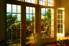 Two sets of hinged patio doors, interior view, at sunset
